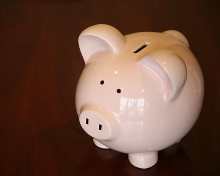 Sparschwein auf einem hölzernen Schreibtisch Standard-Bild - 92620239