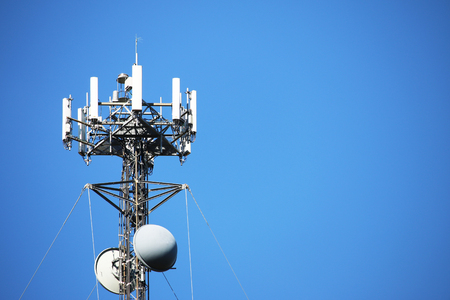 Telecommunications tower set against a blue sky with ample copy space. Also referred to as wireless communications tower. Standard-Bild - 92612227