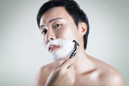 and the horizontal man: Asian man is shaving