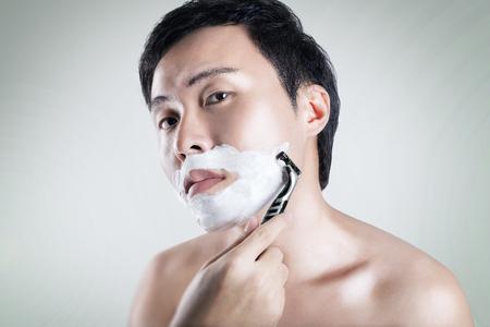 Asian man is shaving