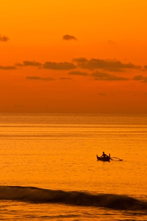 sunset over the sea and fisherman photo
