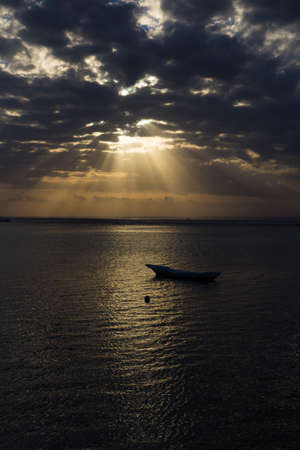 Boat in the sea at sunrise with rays of light coming through the clouds