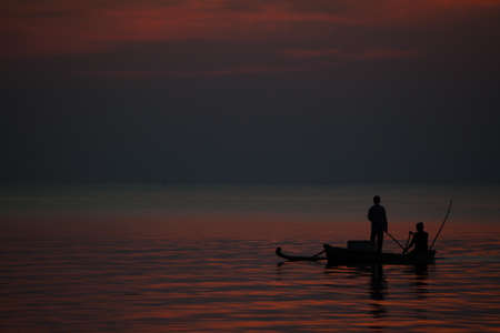 Fishermen in their boat under a red sunset Stock Photo
