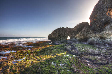 Rocks and cliffs in the sunlight on Ngobaran beach, Indonesia Stock Photo