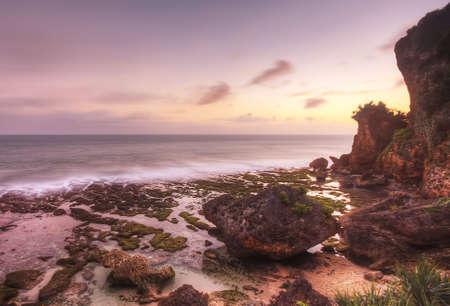Rocks at Ngobaran beach during a pink sunset