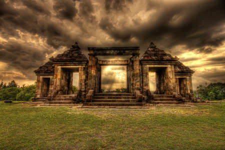 Gateway to Ratu Boko temple in Indonesia with rain clouds looming above