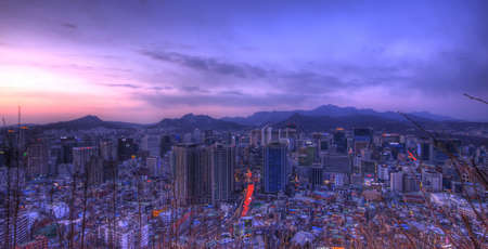 The city of Seoul with mountains in the background at blue hour Stock Photo