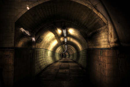 Inside the dark, pedestrian Tyne tunnel with the shadow of a person walking through it