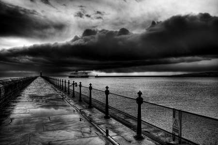 Wet Tynemouth Pier on a gloomy day in black and white