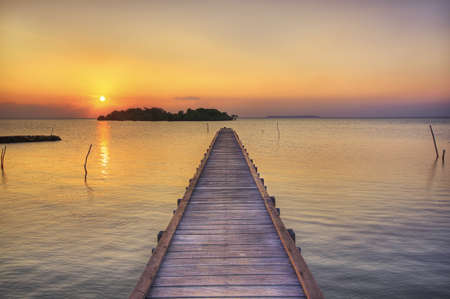A wooden pier and small island at sunset in Karimunjawa Stock Photo