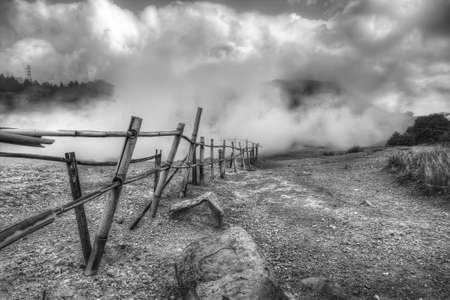 Ramshackle fence around a geyser in black and white