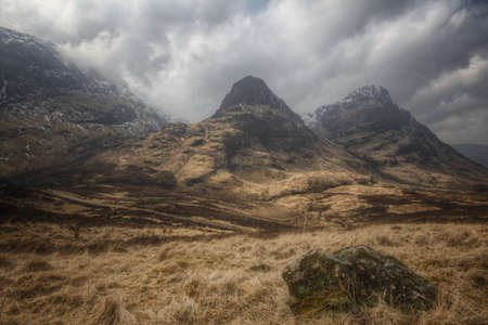 Snowy mountains with dark clouds above in Glencoe, Scotland Stock Photo