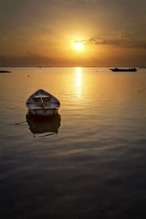 Boat in the sea at sunset in Nusa Lembongan Stock Photo