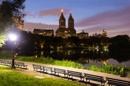 Park benches and lake in Central Park with the San Remo building