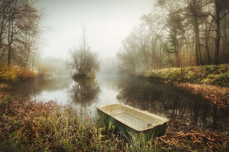 Boat on an eerie lake in the mist in France Stock Photo - 22143077