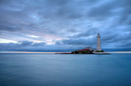 Lighthouse in the sea at blue hour in the morning Stock Photo