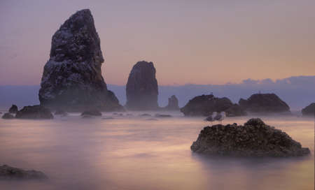 Rocks and pink sunset on Cannon beach, Oregon, USA Stock Photo