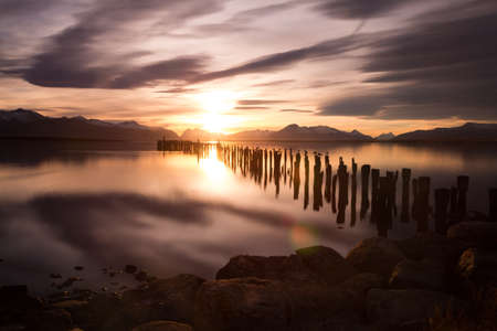 Sticks and rocks in the lake at sunset in Puerto Natales, Chile Stock Photo
