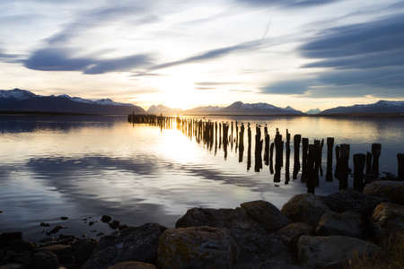 puerto natales: Sticks and rocks in the water at sunset in Puerto Natales, Chile
