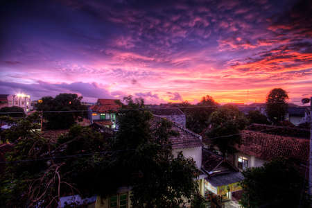 Pink and purple sunset over houses in Indonesia