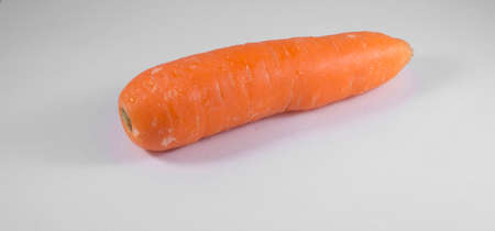 Single carrot on a plain background with a shadow Stock Photo