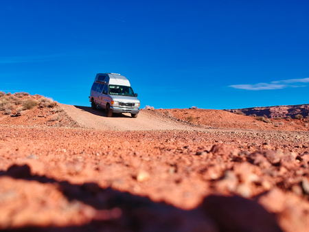 areal view of vehicle driving on the dry landscape of nevada, california and utah in a summer days with blue sky
