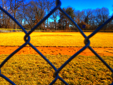 baseball dugout: Baseball field through a metal fence