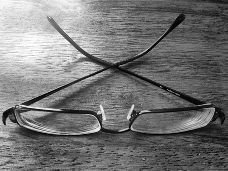Black and white of eye glasses on a wood table