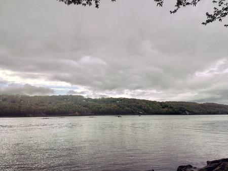 灰色の雲と天気の悪い川の眺め