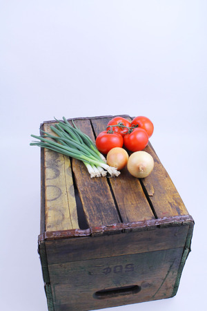 Table onions, tomatoes, whole onions, lying on wooden crate  photo