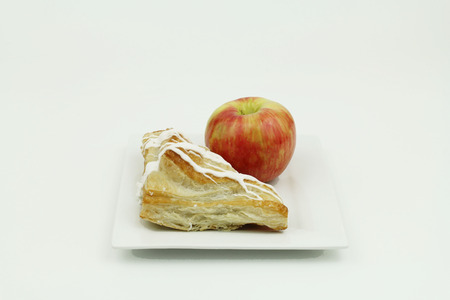 turnover: Turnover on white plate with whole apple