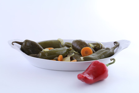 Picled jalapeno peppers with sliced carrots and onions in a white dish with red pepper lying next to dish  Banco de Imagens