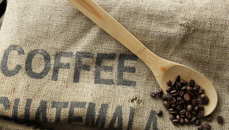 Coffee Beans on wooden spoon and burlap coffee bag