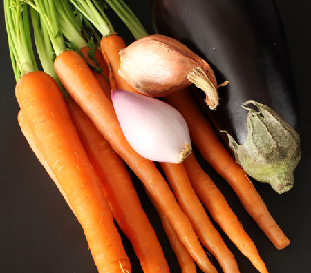 egg plant: Fresh Vegetables of carrots, shallots and egg plant isolated on black background