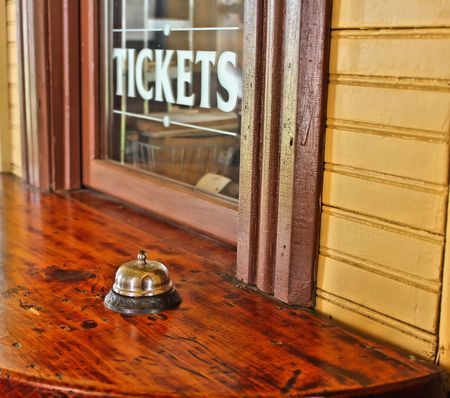 service bell: Ticket window with service bell on wooden counter.