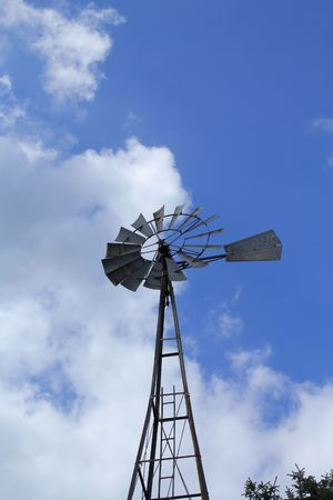 airstream: Old  farm windmill with sky in background.