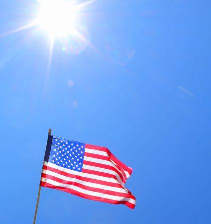 sun burst: American flag with sun burst and clear blue sky.
