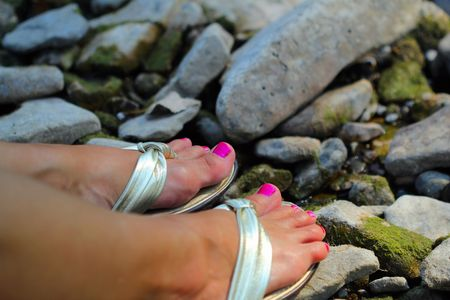wearing sandals: Ladys feet with painted toe nails wearing shiny sandals resting on rocks. Stock Photo