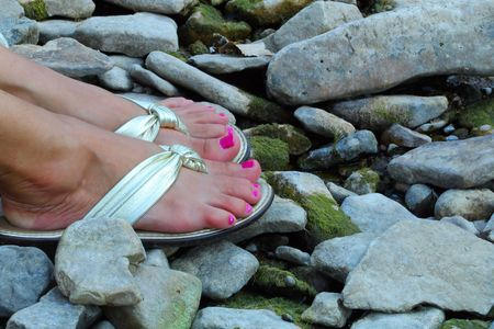 womans: Womans feet with toe nails painted in shiny sandals resting on rocky shoreline.