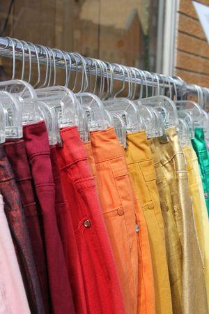 hangers: Colorful denim jeans on hangers. Stock Photo
