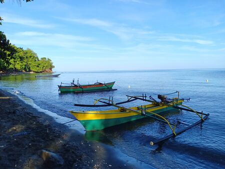 Two traditional wooden fishing boats on the black sandy beach in the morning. Blue sky, calm beach, horizon  and green trees.
