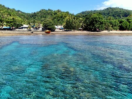 The beach with blue clear crystal water in front of fisherman village on island and the background is green hills and blue sky. Stock fotó