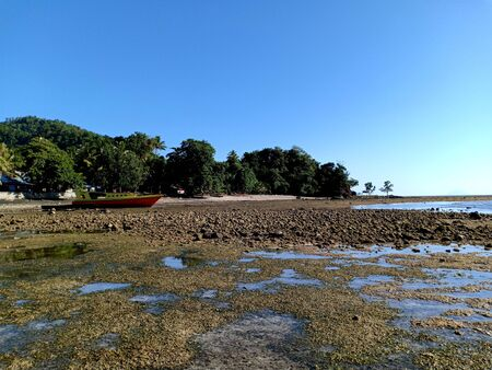 A boat stranded on the beach during low tide on sunny day at fisherman village