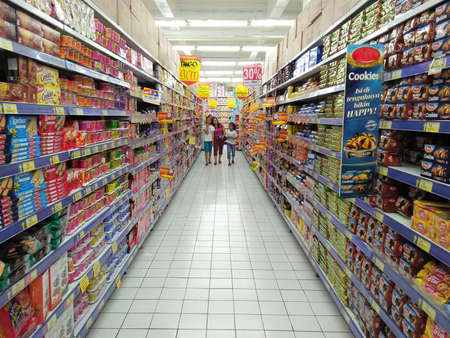Manado, Indonesia - November 26th, 2016; A mother and two daughter walking on the supermarket aisle in snacks area