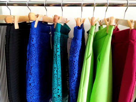 Latest women skirts with various colors are hanging on wooden hangers nicely. Colorful embroidery dress. 版權商用圖片