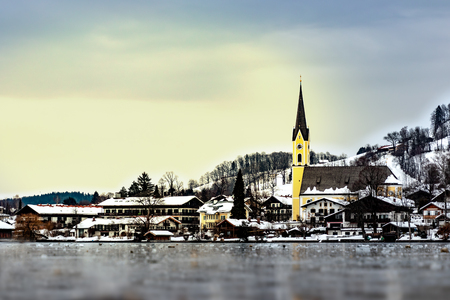 The frozen lake 'Schliersee' in Bavaria, germany, in winter with yellow church St. Sixtus and houses with snow in the back