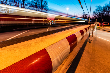 A closed railway barrier in germany with a train in motion and cars waiting