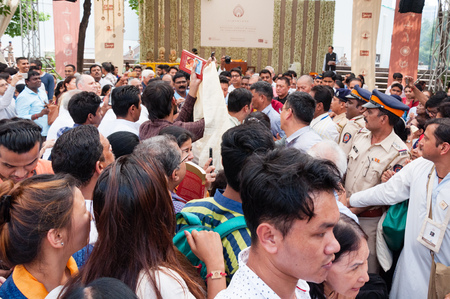 MUMBAI, INDIA – December 10 2017: Crowds jostle to see and photograph the His Holiness the 14th Dalai Lama (Buddhist spiritual head), as is escorted at an event. Security policemen look on.