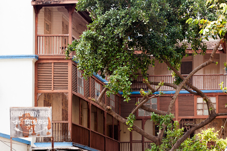 MUMBAI, INDIA – October 23 2017: Church Mission House near Girgaon, Grant Road east, built in 1921.  Wooden balconies and trees are visible. Editorial