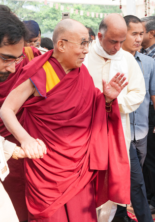 MUMBAI, INDIA – December 10 2017: His Holiness the 14th Dalai Lama waves to people as he is escorted by volunteers at a spiritual lecture event at Somaiya college.